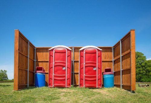 Two red portable toilets rented for a construction and home improvement project