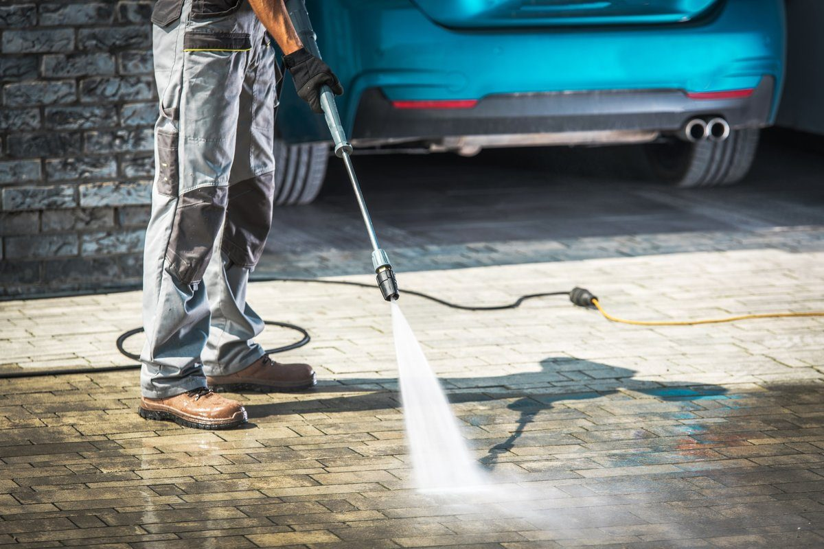 Brick driveway being pressure washed by a professional