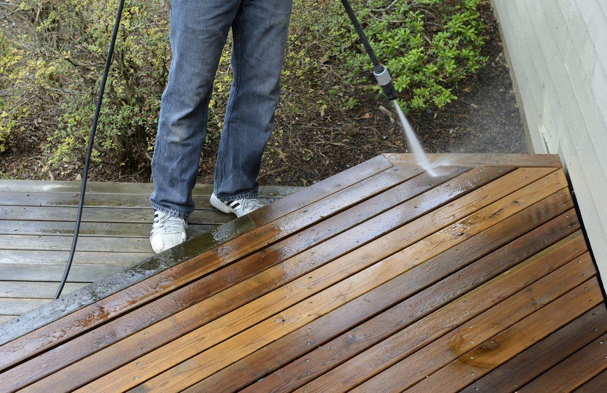 Professional using a pressure washer to clean cedar deck