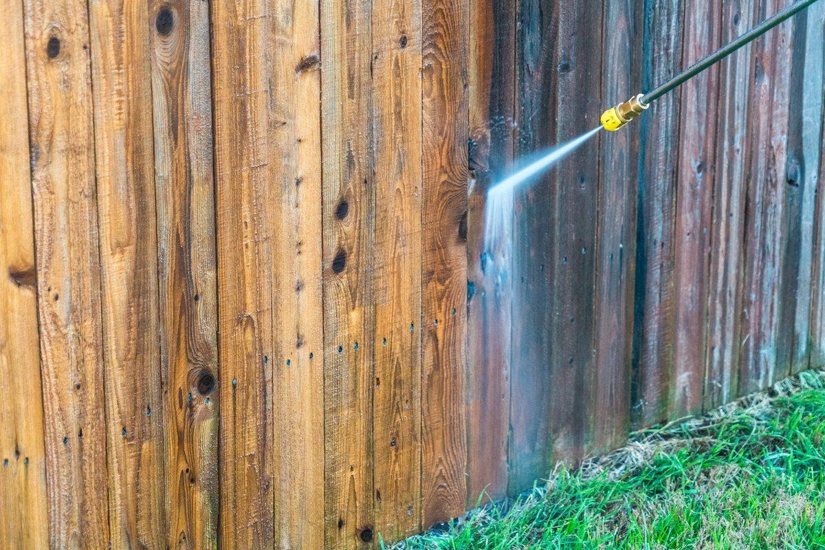 Professional pressure washing a cedar fence