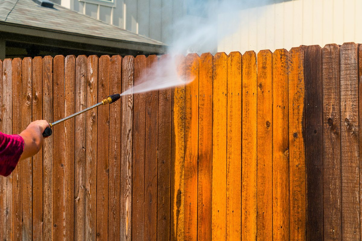 Professional pressure washing a wooden fence