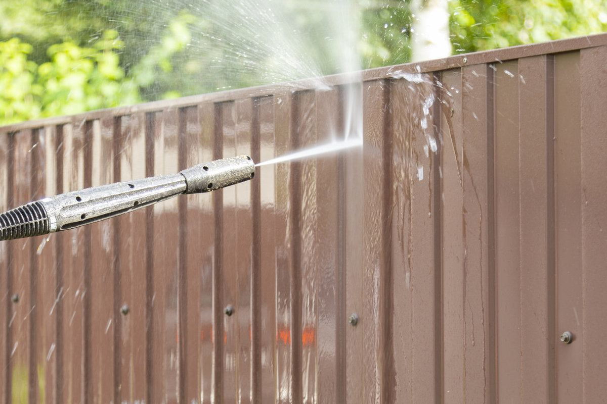 Professional cleaning a fence with high pressure washer