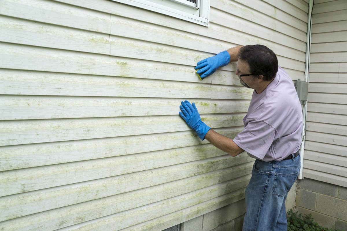Contractor repairing vinyl siding of a customers home