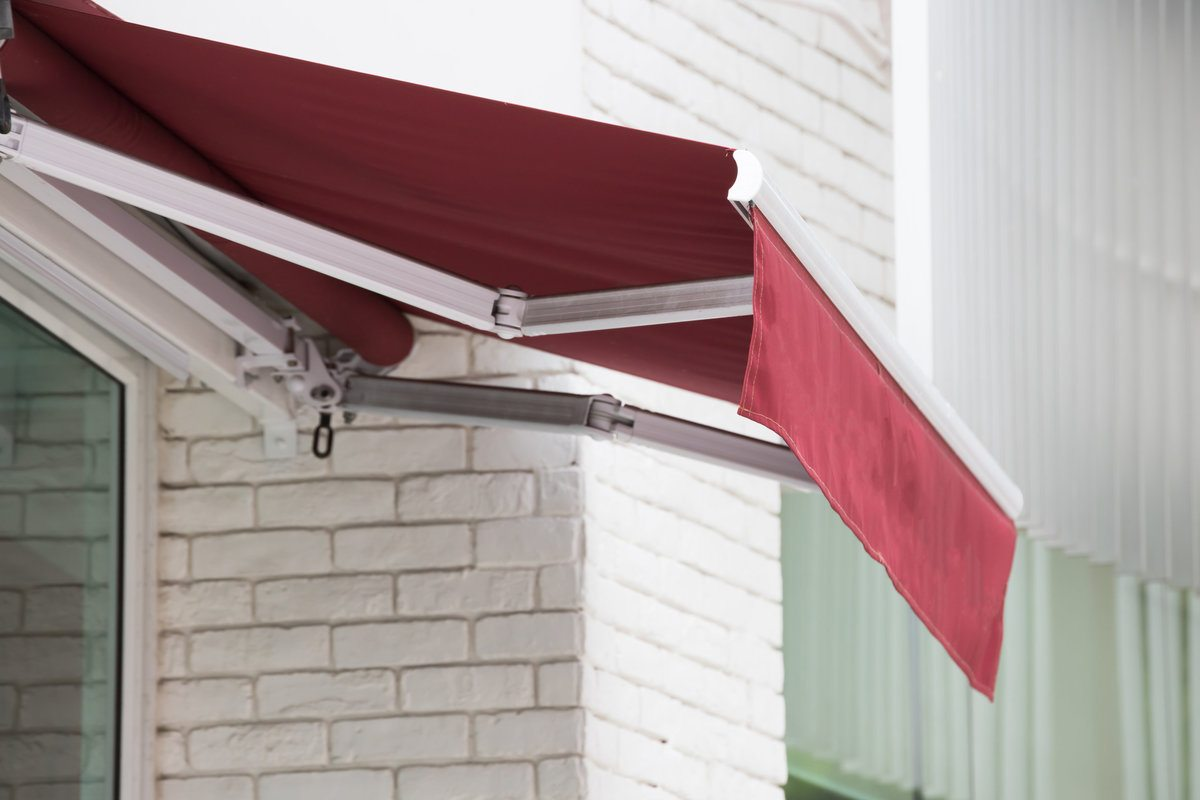 Red retractable awning installed on a house window