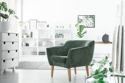 Green armchair in a modern room decorated in white