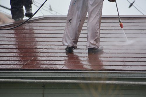 Professional roof cleaner pressure washing a reddish roof