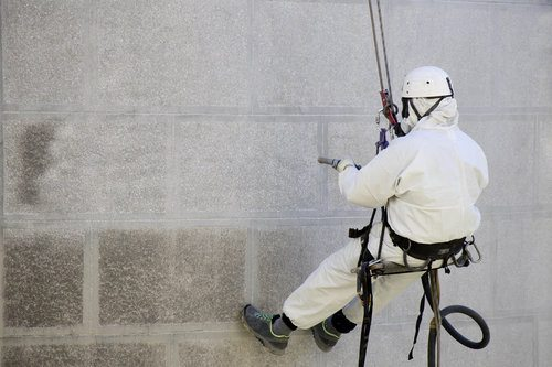 Professional wearing protective clothes is sandblasting a wall using a compressor in order to remove layers of different substances from the surface