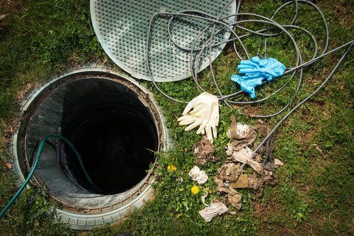 Open access hatch of a septic tank being repaired next to some pairs of gloves