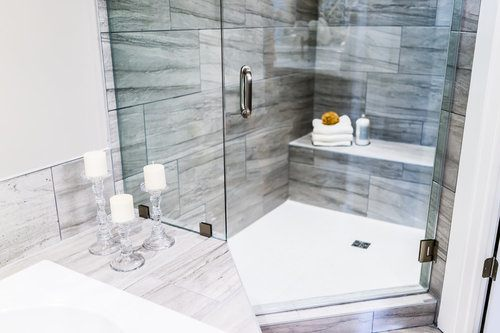 Modern bathroom with marble countertops and a glass shower door