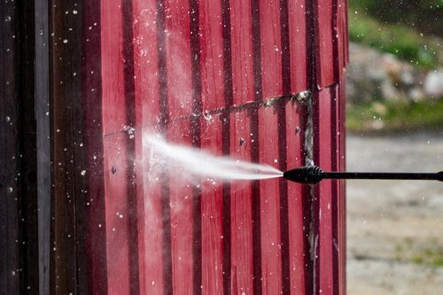 Red metal siding being cleaned with high-pressure water