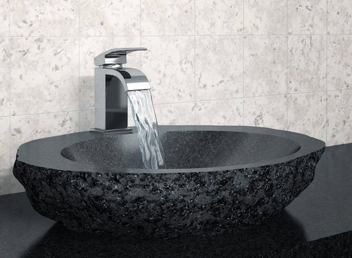 Bathroom faucet with flowing water and black stone sink