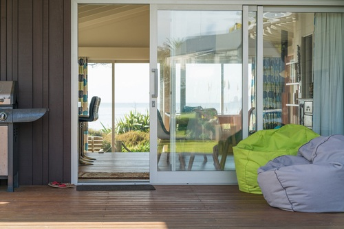 Sliding patio door with several panels that leads into a living room