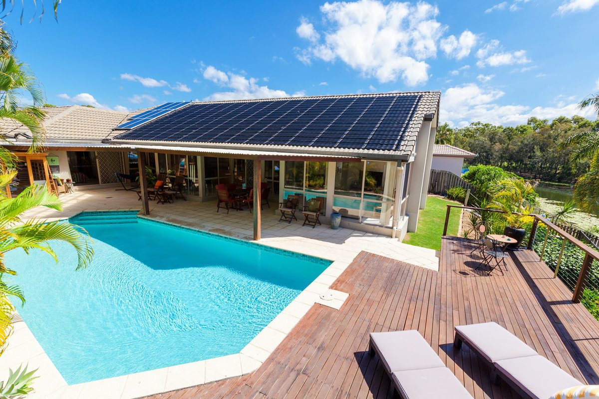Backyard with swimming pool and a solar pool heater on the roof