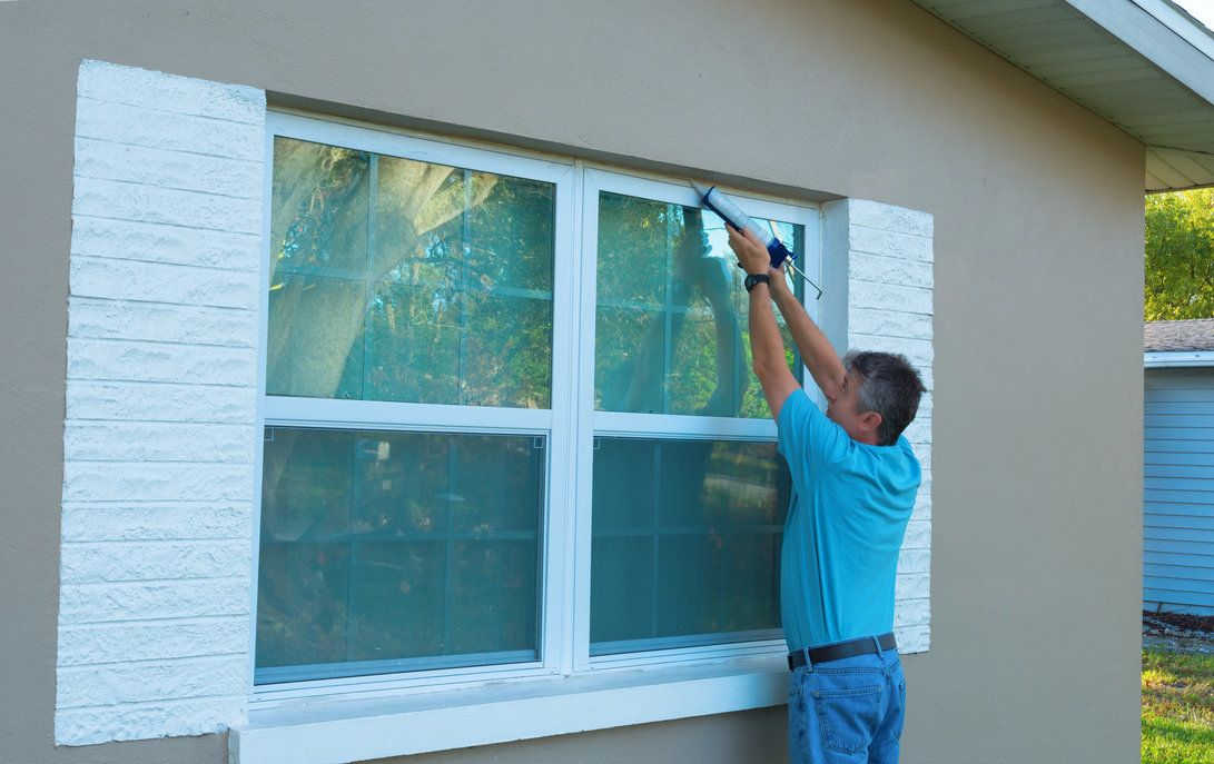 A man installing a storm window