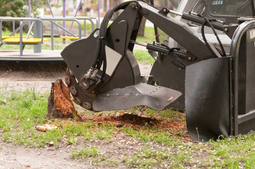 Machine grinding a stump surrounded by grass
