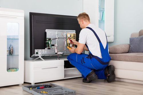Contractor repairing TV in a modern living room