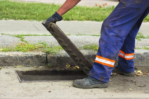 Professional opening a hatch in the street to unclog the main sewer line