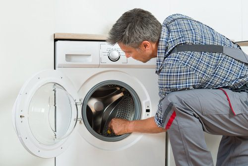 Plumber repairing domestic washing machine