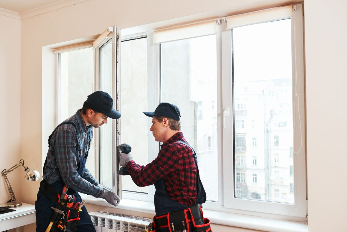 Professionals working inside of a house replacing a window glass