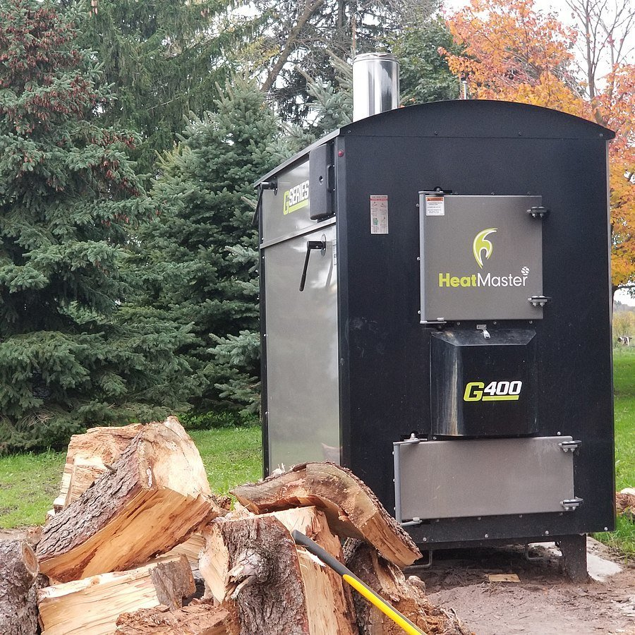 Outdoor Wood Boiler Next to a Pile of Wood