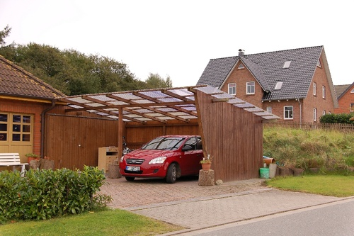 Wooden carport with flat roof and a red car inside