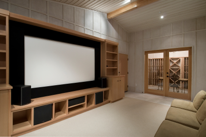 Amazing home theater installed in the basement of a house with a LED TV, audio setup and speaker stands