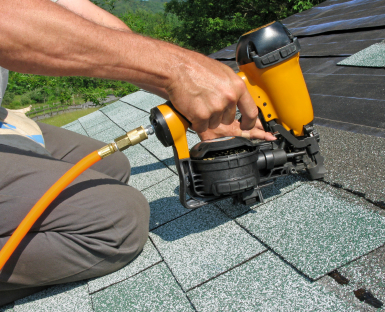 Professional roofer replacing roof shingles using a nail gun