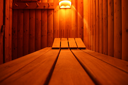 Wood sauna with a light fixture in the background