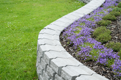 Stacked stone retaining wall with purple flowers at a residential home