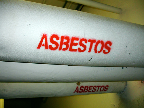 Asbestos Warning Sign on Building Pipes